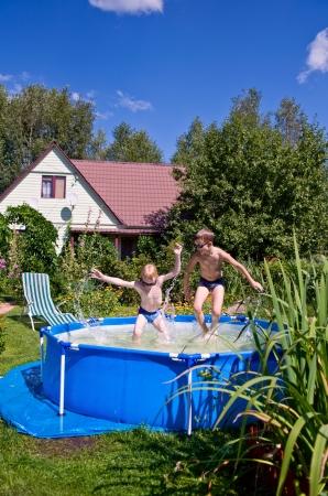 二人の少年ジャンプと屋外のスイミング プールで水しぶき 写真素材