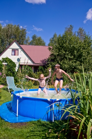 dacha: two boys jumping and splashing in swimming pool outdoors Stock Photo