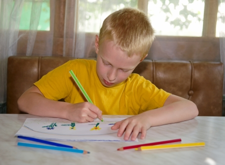 young boy drawing positive picture with pencils photo