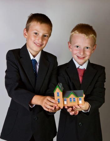 two boys wearing suits holding toy house photo