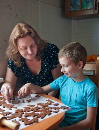 mother and son making gingerbread cookies photo