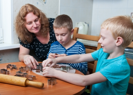 mother and two sons making gingerbread cookies photo