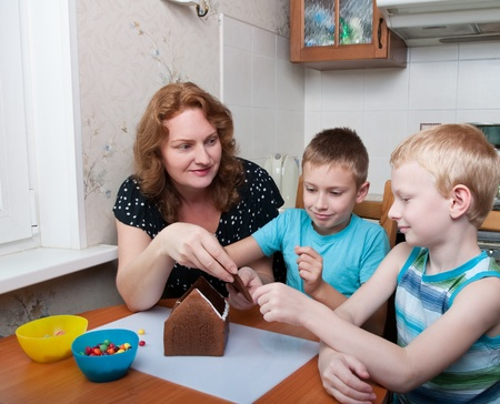mother and two sons making gingerbread house photo