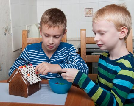 two brothers decorating gingerbread house, christmas time photo