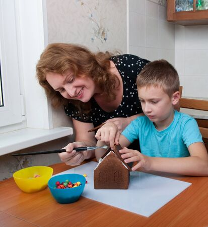 mother and son making gingerbread house, christmas time photo