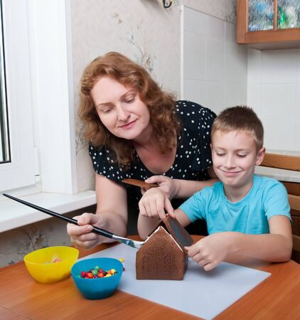 mother and son decorating gingerbread house, christmas time photo