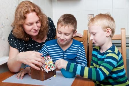 母と二人の息子のジンジャーブレッドハウスを飾る