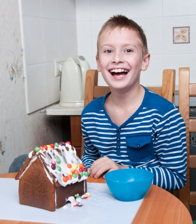 young boy making gingerbread house and laughing photo