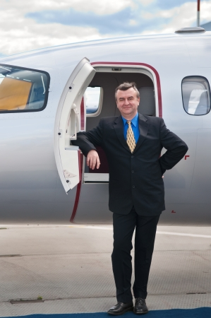 Smiling Businessman at Corporate Jet photo