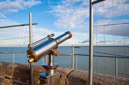 Telescope aiming Atlantic Ocean and island Tombelaine on view point on Mont Saint-Michel, France photo