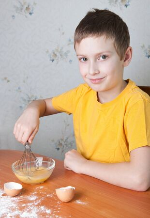 Young boy shaking up eggs and baking photo