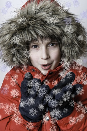 Young boy wearing warm red jacket with fur blowing on snow flakes photo