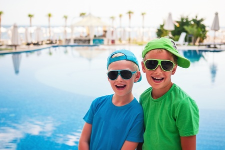 Two smiling brothers at the swimming pool photo