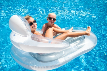 Two brothers having fun playing on a floating mattress in a swimming pool photo