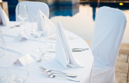 round table: Table setting for a wedding ceremony at swimming pool