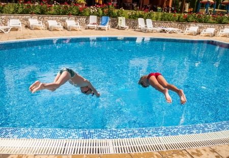 10 11 years: Two boys jumping into a pool