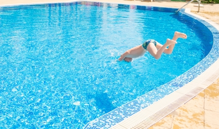 A boy jumping into swimming pool