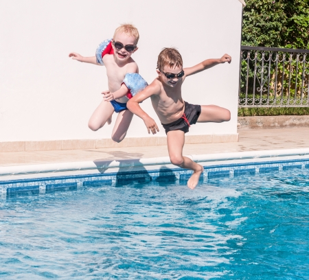 Two happy boys jumping into swimming pool photo