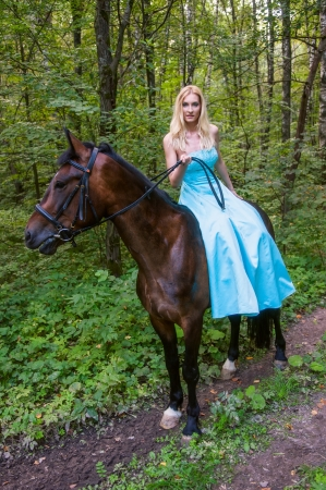 Young pretty girl on horseback in the forest photo