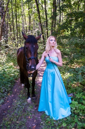 Young pretty girl and a horse in the forest photo