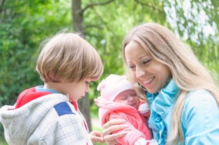 Jonge moeder met haar kinderen in het bos Zoon is jaloers moeder van jongere zus