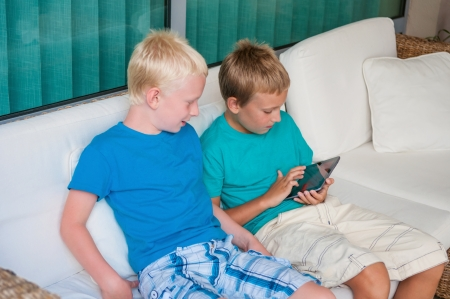 Two brothers playing on touchscreen tablet computer photo