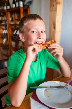 Young boy eating pizza at restaurant photo