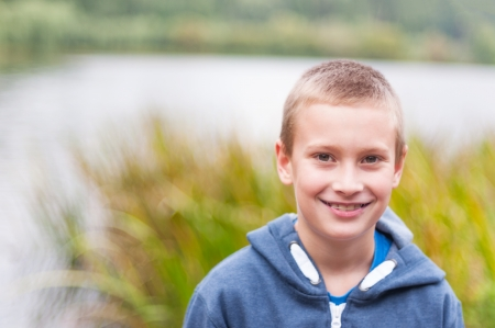 Adorable boy with retainer on teeth smiling outdoors photo