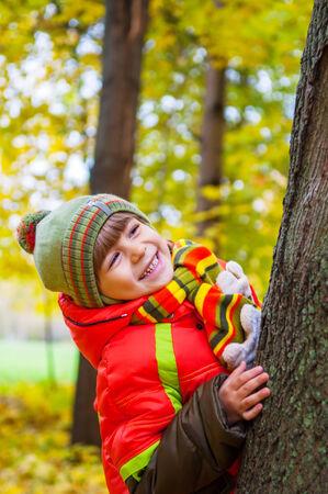 幸せな子供の笑顔と秋の公園の中に隠れて