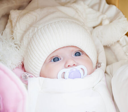 Adorable baby girl wearing white winter hat photo