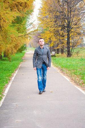 秋の公園で歩く若いハンサムな男 写真素材