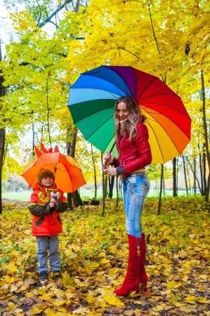 秋の公園で明るい色とりどりの傘で幸せな家族