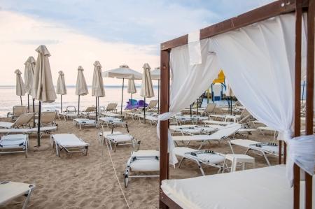 sunbeds: Gazebo bed, sunbeds and umbrellas in sand beach Stock Photo