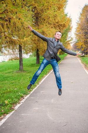 秋の公園でジャンプ若いハンサムな男