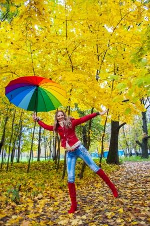 秋の公園で明るく色とりどりの傘を持つ美少女