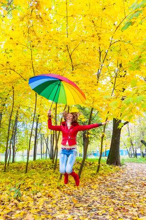 秋の公園でジャンプ明るい色とりどりの傘できれいな女の子