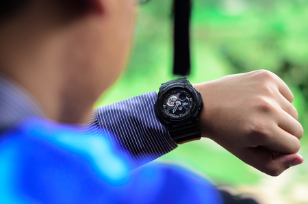 graduation suit: A male university graduate is looking at the time on his wrist watch. Soft focus, shallow DOF with bokeh background.