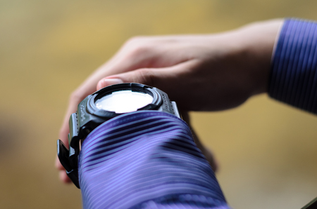 graduation suit: Man holding his hand while wearing a black wrist watch.Soft focus, shallow DOF with bokeh background.