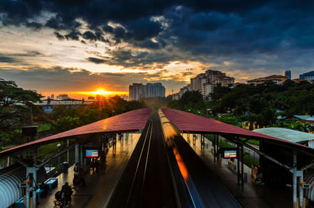 actively: Dramatic sunrise at KTM Segambut Train Station, Kuala Lumpur, Malaysia. It can be seen that people are still actively using public transportation even on weekends.