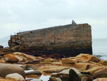 pesca en la orilla solitaria roca Foto de archivo