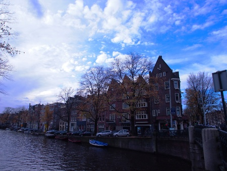 Canal side houses under blue cloudy sky