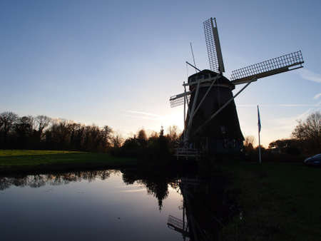 traditional windmill: Amsterdam traditional windmill silhouette with pond reflection at dust time Stock Photo
