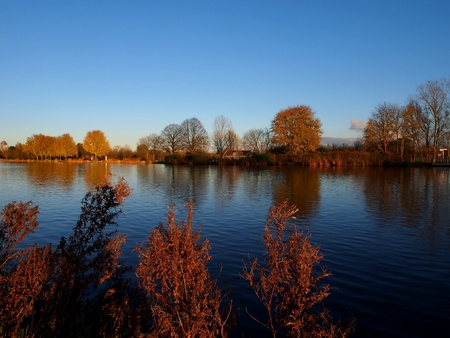 Autumn river bank reflection under blue sky Stock Photo
