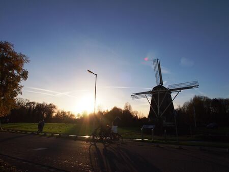 Cycling family and walking couple with traditional windmill at dust