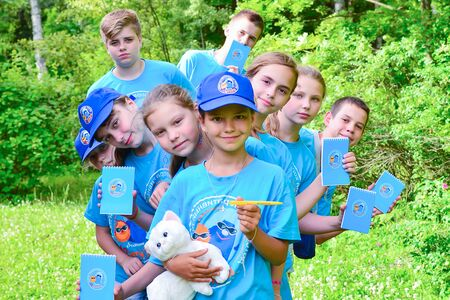 Summer camp for gifted children - children's science city. In the photo, children in identical camp shirts are holding notebooks. Éditoriale