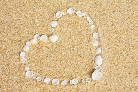 love symbol on sand at beach photo