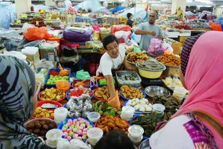 TERENGGANU, MALAYSIA-APRIL 16:Unidentified traditional food traders are treating some of the guests in Pasar Kedai Payang, Terengganu Malaysia on April 16, 2012. Pasar Kedai Payang is a popular destination for local and foreign tourists