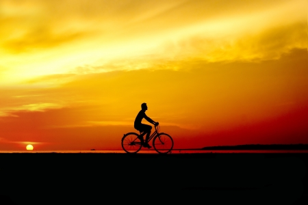 silhouette of the cyclist riding at sunset photo