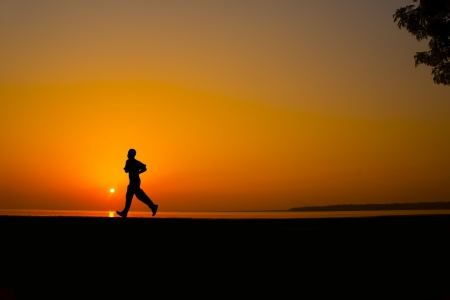 Silhouette man jogging on great sunset background Stock Photo