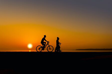 cyclist and walker silhouette on sunset photo